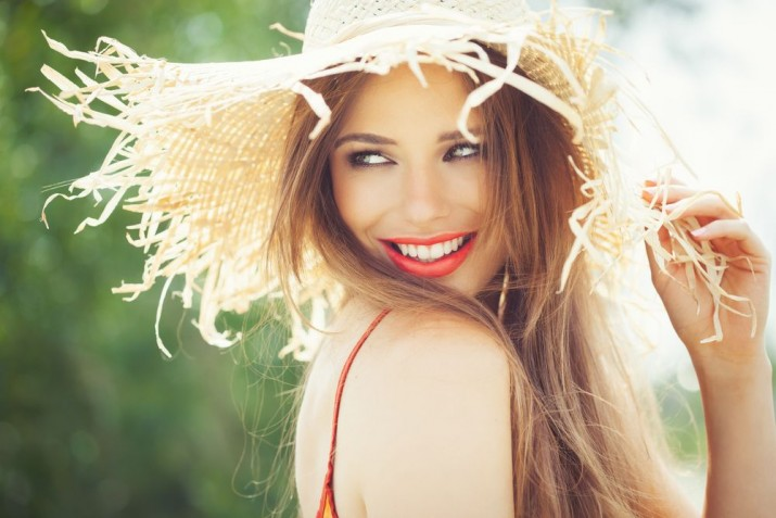 Young woman in straw hat smiling in summer outdoors.